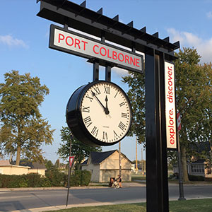 36-inch diameter double-faced Suspended Bracket Clock mounted below a sign for Port Colborne Transit Station, in Port Colborne, Ontario, Canada. Background of blue sky.