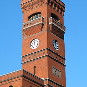 Brick clock tower with a set of 2 60-inch diameter inset tower clocks. This Romanesque style Brick building houses the US Forestry Services , it is known as the Sidney Yates Building, and is located in Washington DC. The 2 clocks are a set of 3, Roman Style clocks. Background of blue sky.