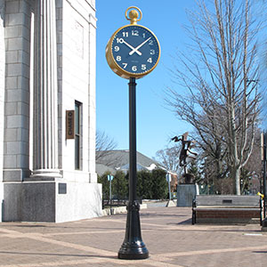 30-inch diameter Double-face Post clock with gold pocket-watch winder top, with a white numerals on a black clock dial, located in front of a bank building, with a blue clear sky background