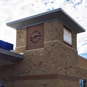 Clock Tower with a 72-inch diameter Marker-style or skeletal style Clock, in a modern style with black powdercoat-finish hour markers, and straight tapered hands.  On a brown and tan brick tower fascia.  This clock is located at St. David's FSED.